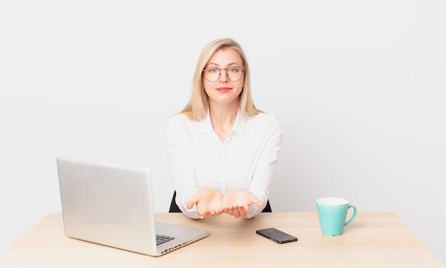 Mulher bonita loira jovem loira sorrindo feliz com simpática e oferecendo e mostrando um conceito e trabalhando com um laptop