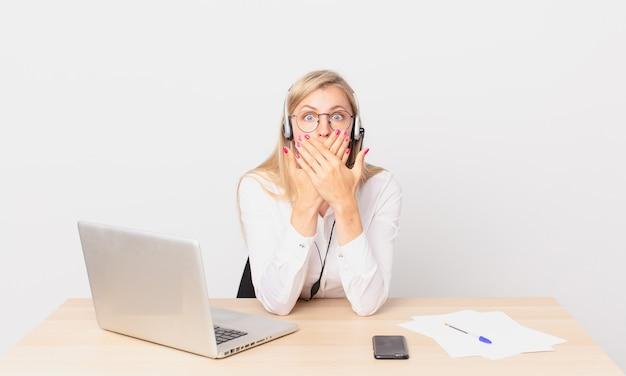 Mulher bonita loira jovem mulher loira cobrindo a boca com as mãos com um choque e trabalhando com um laptop