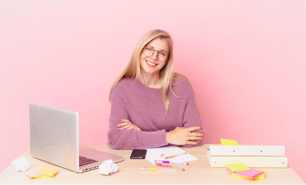 Mulher bonita loira jovem mulher loira sorrindo alegremente com uma mão no quadril, confiante e trabalhando com um laptop
