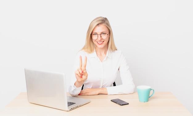 Mulher bonita loira jovem mulher loira sorrindo e parecendo amigável, mostrando o número dois e trabalhando com um laptop