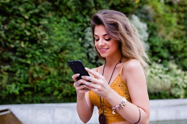 Mulher bonita loira jovem na rua, usando telefone celular e sorrindo. verão, fundo verde