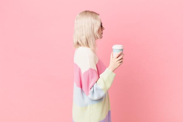 Mulher bonita loira na vista de perfil, pensando, imaginando ou sonhando acordada. conceito de café