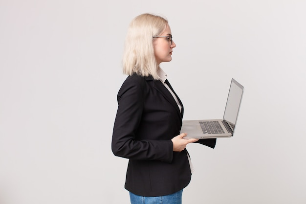 Mulher bonita loira na vista de perfil pensando, imaginando ou sonhando acordada e segurando um laptop