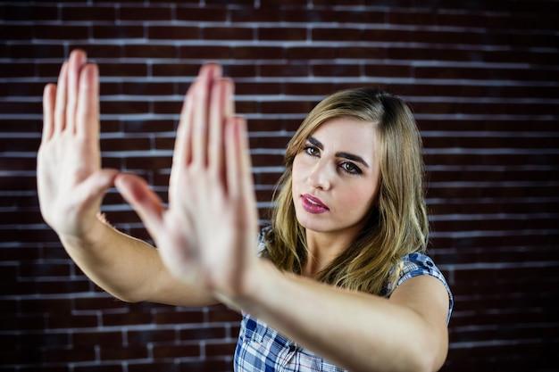 Mulher bonita loira olhando através das mãos