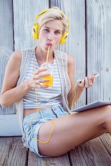 Mulher bonita loira ouvindo música com seu telefone celular e bebendo suco de laranja