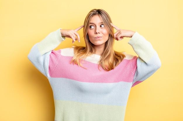 Mulher bonita loira parecendo concentrada e pensando seriamente em uma ideia, imaginando uma solução para um desafio ou problema