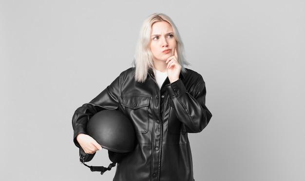 Mulher bonita loira pensando, sentindo-se duvidosa e confusa. conceito de motociclista