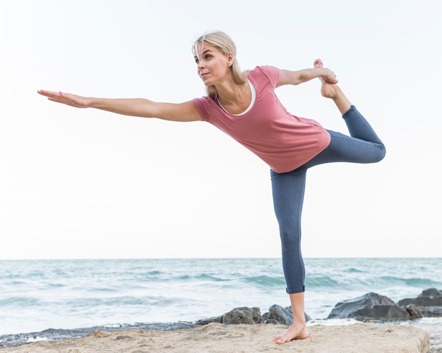 Mulher bonita loira praticando ioga ao ar livre