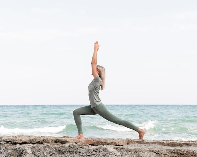 Mulher bonita loira praticando ioga na praia