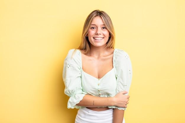 Mulher bonita loira rindo tímida e alegre, com uma atitude amigável e positiva, mas insegura