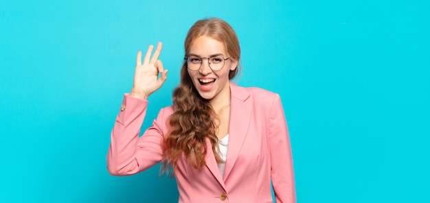Mulher bonita loira se sentindo bem-sucedida e satisfeita, sorrindo com a boca bem aberta, fazendo sinal de ok com a mão