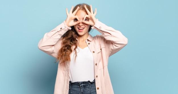 Mulher bonita loira se sentindo chocada, maravilhada e surpresa, segurando os óculos com olhar surpreso e incrédulo