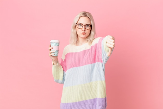 Mulher bonita loira se sentindo mal, mostrando os polegares para baixo. conceito de café
