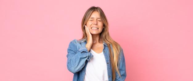 Mulher bonita loira segurando a bochecha e sofrendo de dor de dente dolorida, sentindo-se doente, miserável e infeliz, procurando um dentista