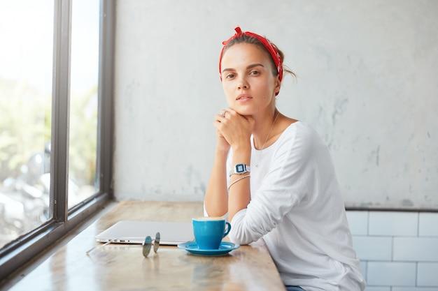 Mulher bonita loira sentada em um café