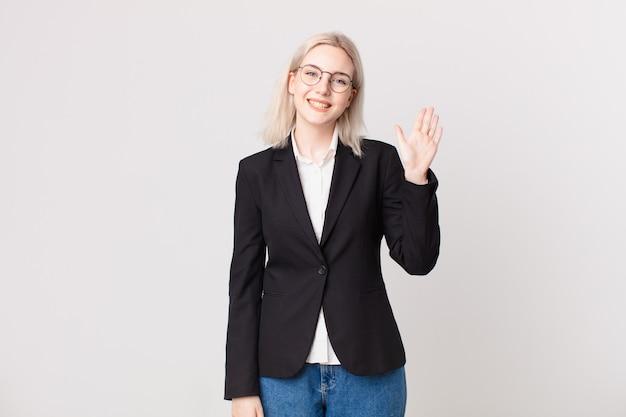 Mulher bonita loira sorrindo alegremente, acenando com a mão, dando as boas-vindas e cumprimentando você. conceito de negócios