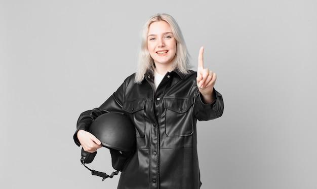 Mulher bonita loira sorrindo com orgulho e com confiança, fazendo o número um. conceito de motociclista