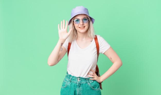 Mulher bonita loira sorrindo e parecendo amigável, mostrando o número cinco. conceito de verão