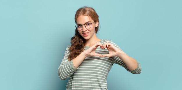 Mulher bonita loira sorrindo e se sentindo feliz, fofa, romântica e apaixonada, fazendo formato de coração com as duas mãos
