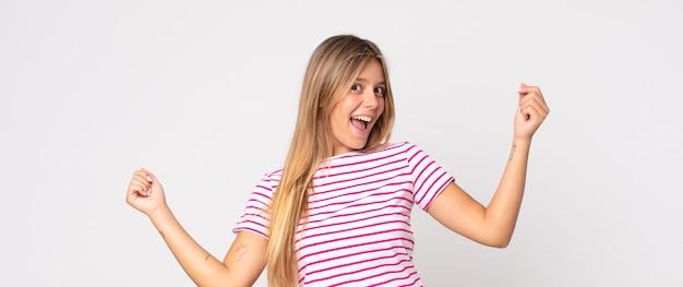 Mulher bonita loira sorrindo, sentindo-se despreocupada, relaxada e feliz, dançando e ouvindo música, se divertindo em uma festa