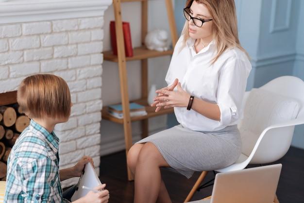 Mulher bonita loira vestindo camisa branca e saia, sentada na cadeira branca, segurando as mãos juntas