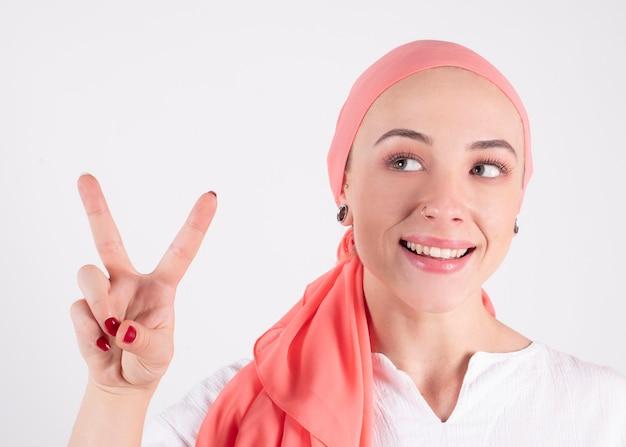 Mulher bonita, lutadora contra o câncer, usa um lenço rosa, faz o símbolo da vitória com os dedos