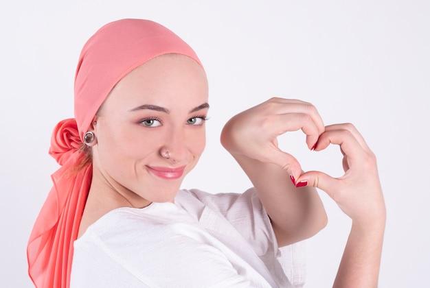 Mulher bonita, lutadora contra o câncer, usa um lenço rosa, faz um símbolo do coração com os dedos