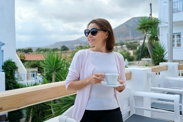 Mulher bonita madura andando com uma xícara de café no hotel resort restaurante ao ar livre. bela pitoresca paisagem montanhosa. recreação, lazer, verão, fim de semana, turismo, viagens pessoas de meia-idade