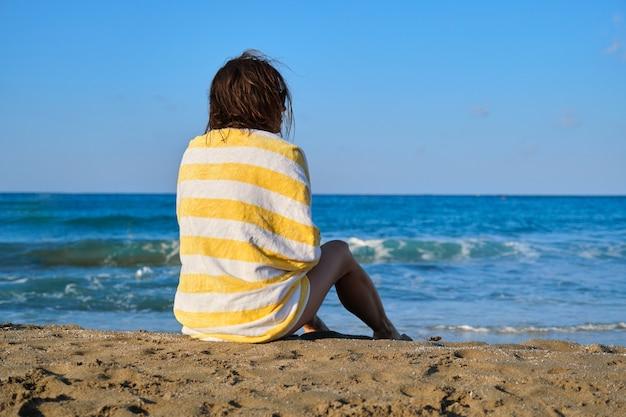 Mulher bonita madura com toalha de praia, sentado na areia, mulher sorridente feliz, apreciando a paisagem do sol do mar. relaxamento, lazer, beleza, oceano, estilo de vida de pessoas de meia-idade