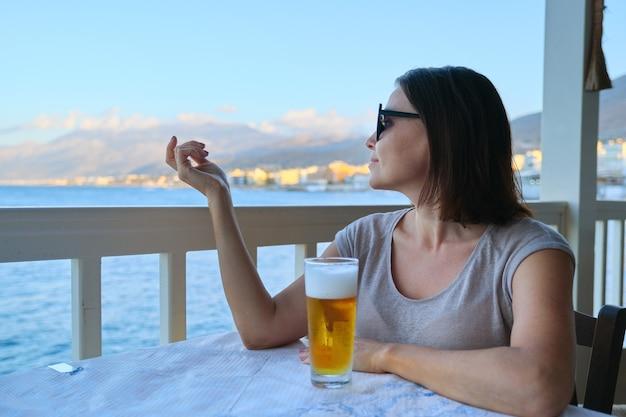 Mulher bonita madura descansando sentado no café do mar com um copo de cerveja gelada. férias de verão, mulher gosta de paisagens de pôr do sol no mar e uma bebida deliciosa, copie o espaço