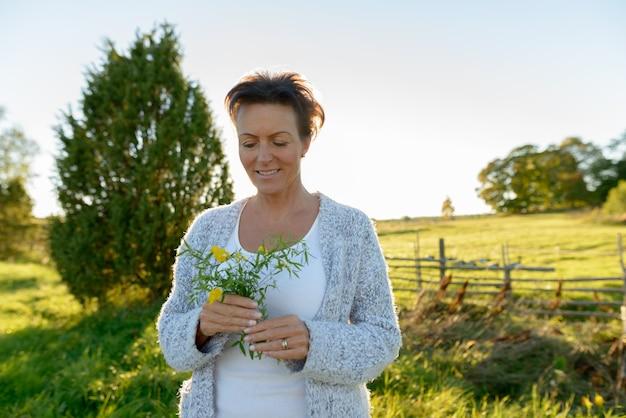 Mulher bonita madura feliz segurando flores em uma planície pacífica e gramada com a natureza
