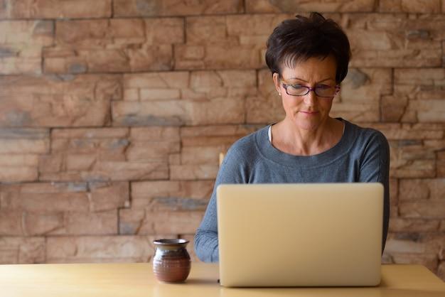Mulher bonita madura usando óculos e usando o laptop na mesa de madeira contra a parede de tijolos