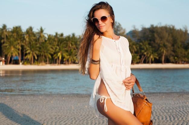 Mulher bonita magro em um vestido branco na praia tropical no pôr do sol segurando a mochila de couro.