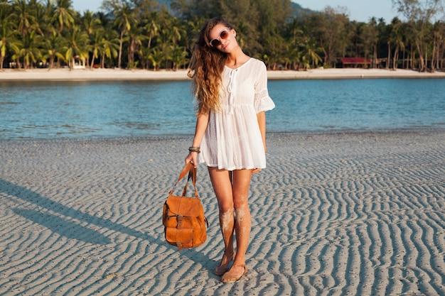 Mulher bonita magro em vestido de algodão branco andando na praia tropical no pôr do sol segurando a mochila de couro.