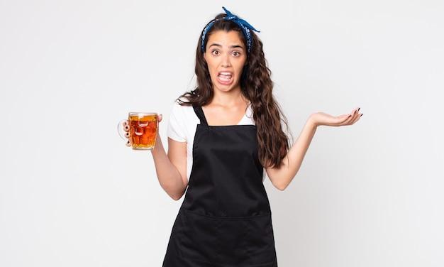 Mulher bonita maravilhada, chocada e atônita com uma surpresa inacreditável e segurando um litro de cerveja