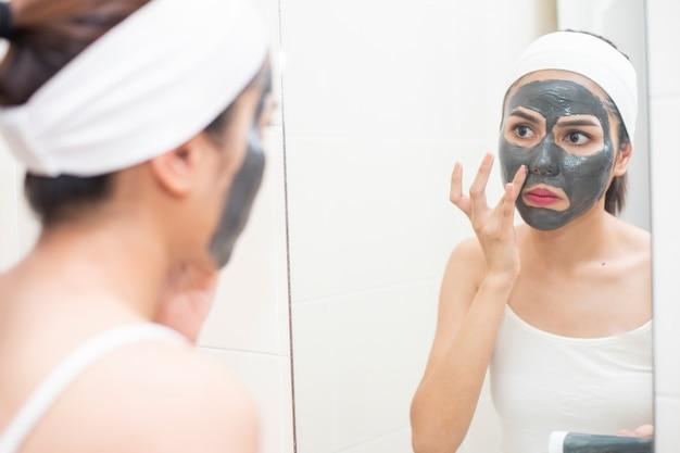 Mulher bonita mascarando o rosto em fundo branco