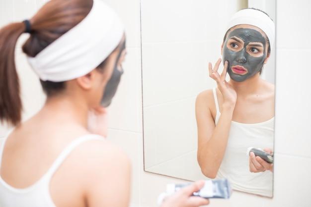 Mulher bonita mascarando o rosto no fundo branco