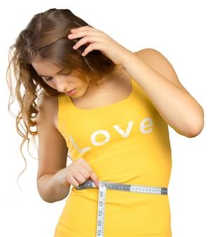 Mulher bonita, medindo a cintura com uma fita métrica