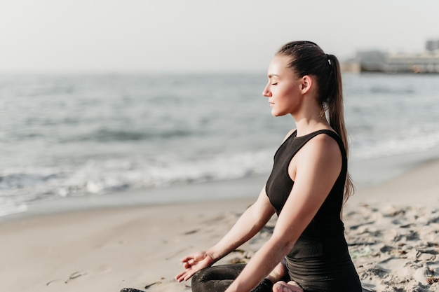 Mulher bonita, meditando e praticando ioga na praia perto do oceano