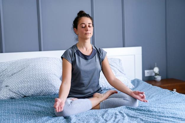Mulher bonita meia idade sentado na cama dela e fazendo yoga com os olhos fechados.