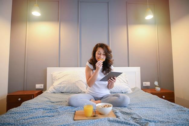 Mulher bonita meia idade tomando café da manhã na cama dela e olhando para o tablet.