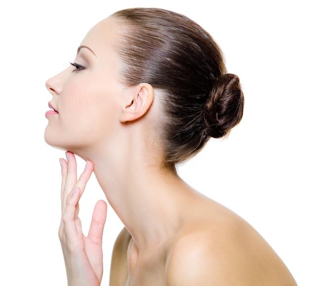 Mulher bonita, mimando o pescoço - em fundo branco. retrato do perfil.