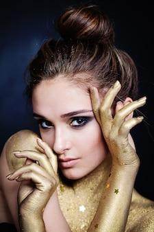Mulher bonita modelo com pele dourada com estrelas e maquiagem glamourosa. close do rosto