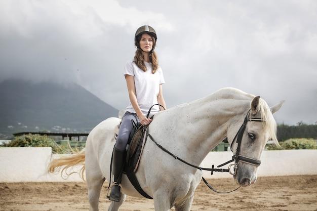 Mulher bonita, montando um cavalo branco