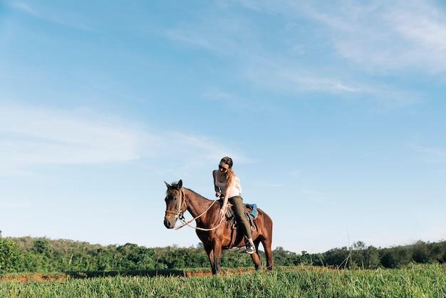 Mulher bonita, montando um cavalo na zona rural.