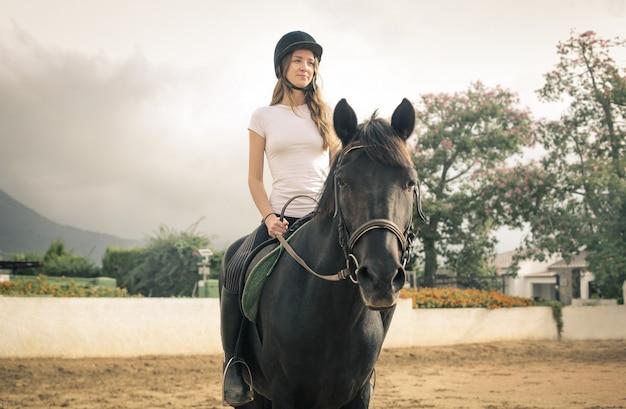 Mulher bonita, montando um cavalo preto
