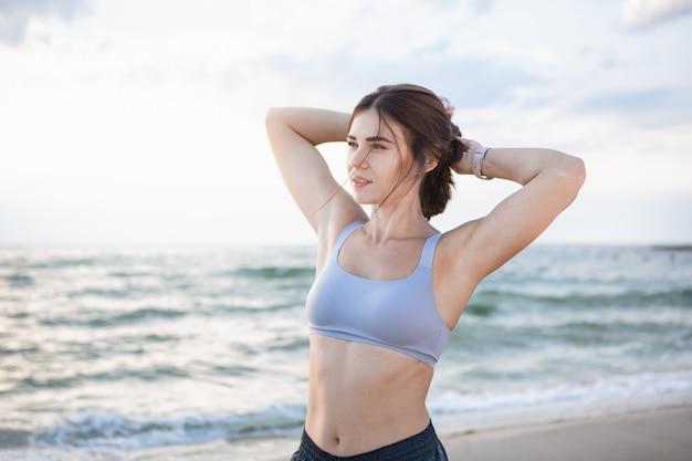 Mulher bonita morena arruma o cabelo após treino na beira-mar ao nascer do sol. modelo ouvindo música durante o exercício perto do mar. conceito de estilo de vida saudável.