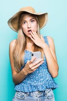Mulher bonita morena chocada com vestido e chapéu de palha briga por smartphone enquanto olha para longe sobre um fundo azul