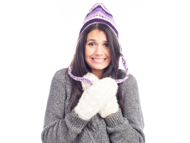 Mulher bonita morena com um chapéu peruano de lã um suéter e luvas que tem frio