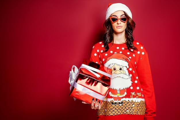 Mulher bonita morena de óculos escuros e pulôver de tamanho grande vermelho com papai noel com caixa de presente